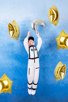 Young child boy male playing in astronaut with silver moon in white astronaut costume and dreaming about flying into cosmos through the stars staying near gold star's balloons