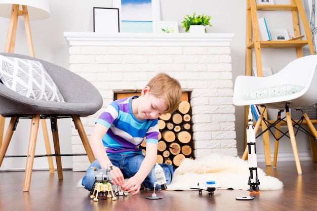 Young child boy male playing with cosmos's toys constructor: rocket, shuttle, rover, satellite and astronaut doll in comfortable interior at home on wooden floor