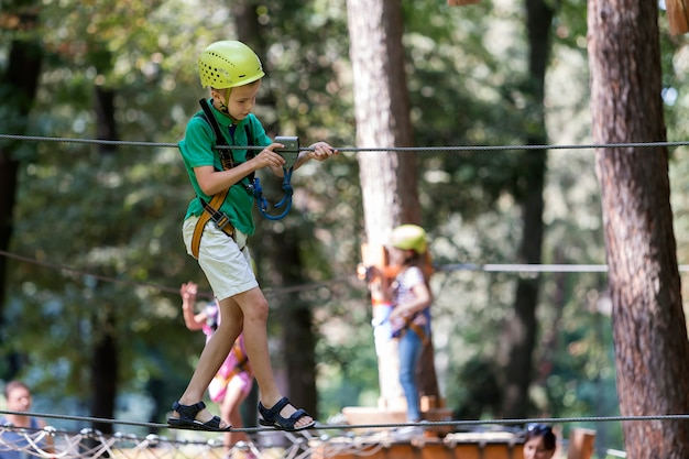 Young child boy on rope way in park.