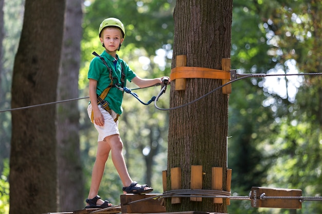 Young child boy in safety harness and helmet attached with carbine to cable on rope way in park.