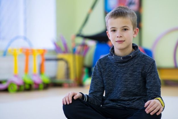 Young child boy sitting and relaxiong on the floor inside sports room in a school after training.