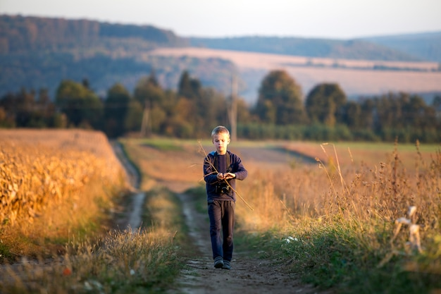 Young child boy with photo camera at wheat field on blurred rural