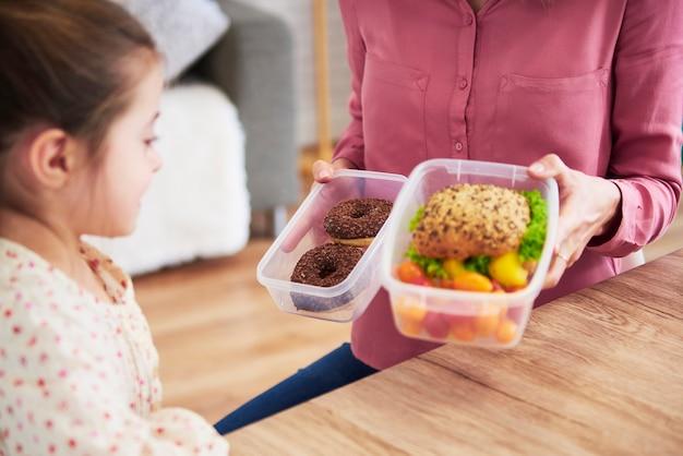 Маленький ребенок выбирает между здоровым сэндвичем и шоколадными пончиками