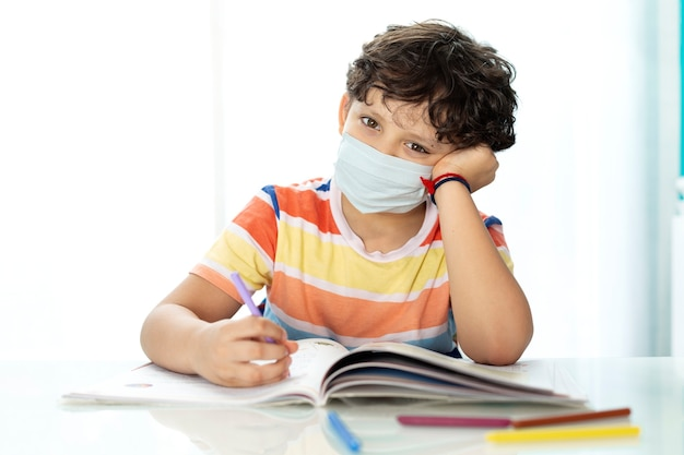 Young child doing homework at home. he is wearing a face mask.