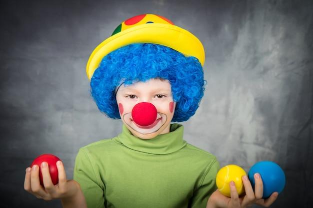가발과 가짜 코를 가진 광대로 옷을 입은 어린 아이는 카니발을 축하하는 다채로운 공을 가지고 노는 재미가 있습니다.