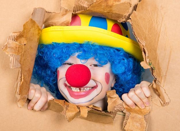 가발과 가짜 코를 가진 광대 복장을 한 어린 아이는 열린 판지에서 보는 재미를 가지고 있습니다.