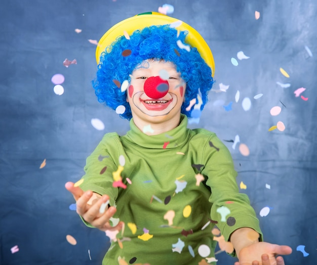 Young child dressed as a clown with wig and fake nose has fun playing with colorful confetti celebrating carnival