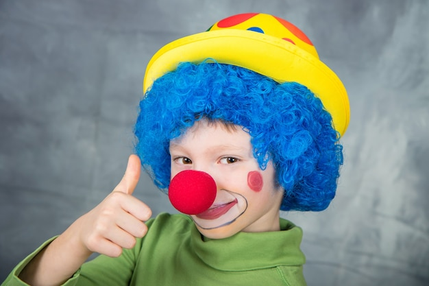 Young child dressed as a clown with wig and fake nose smiling and thumbs up