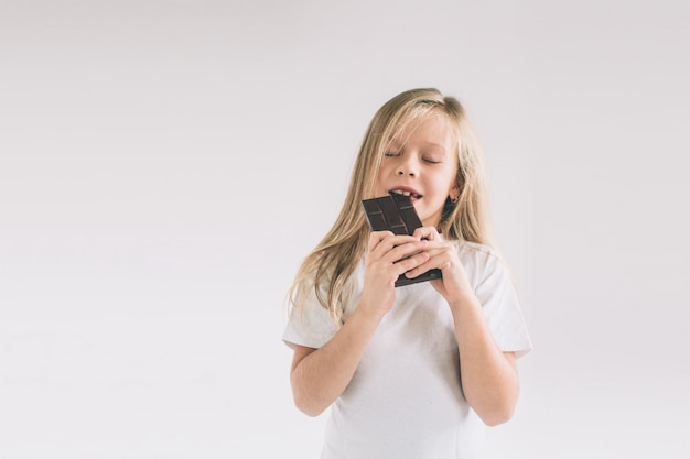Young child eating a chocolate bar. blondy girl isolated on white .