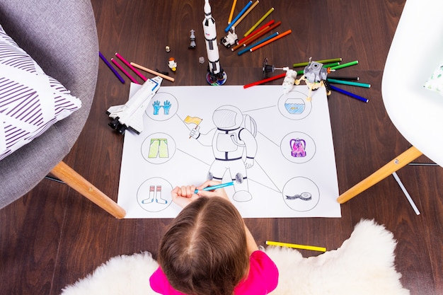 Young child girl female painting astronaut costume by colorful pens and dreaming about cosmos with cosmonaut constructor toys