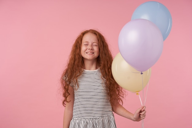 Young child girl, holding colorful balloons, keeps her eyes closed and dream