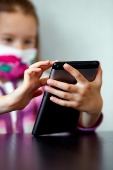 Young child girl at home, wearing a protection mask and gaming on a tablet, coronavirus quarantine. school at home, studying online, learning from home, social distancing. stay at home concept.