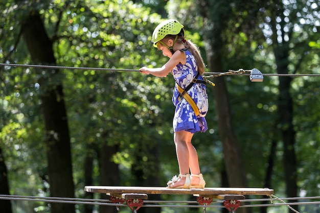 Young child girl on rope way in park.