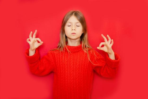 赤い孤立した背景の上に立っている若い子供の女の子は、リラックスして目を閉じて笑顔で指で瞑想ジェスチャーをしています。ヨガのコンセプト