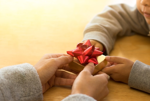 엄마에 게 선물 상자를 전달하는 어린 아이