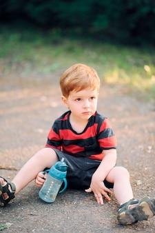 Маленький ребенок в повседневной одежде летом сидит на земле в парке и пьет воду из чашки