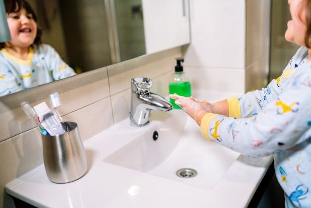 Covid 19 코로나 바이러스 예방 및 보호에서 잠옷을 입고 비누로 손을 씻는 어린 아이
