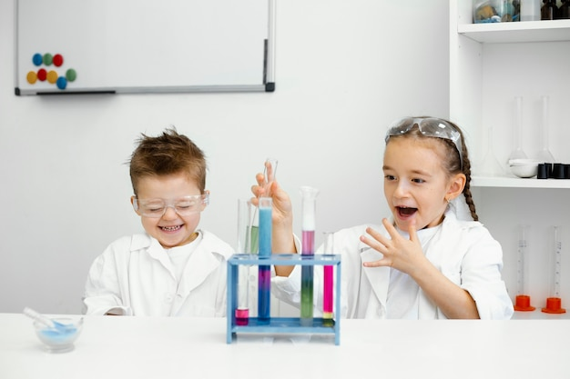 실험실에서 실험을하는 안전 안경을 가진 어린 아이 과학자