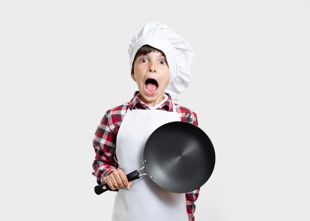 Young child with a pan surprised