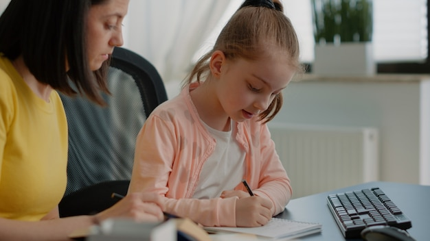 Young child writing homework on notebook and mother assisting