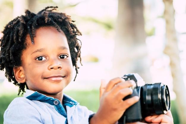 Маленькие дети с черной африканской кожей играют с профессиональным фотоаппаратом на открытом воздухе