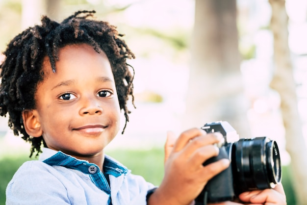 Young children black african skin play with profesisonal photo camera gear in outdoor
