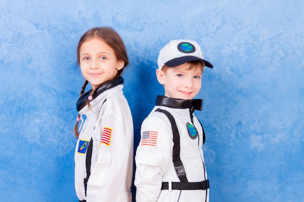 Young children boy and girl playing in astronaut in white astronaut costume and dreaming about flying into cosmos