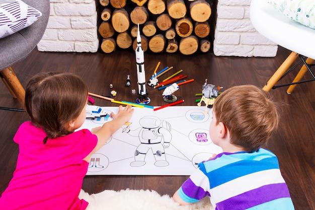 Маленькие дети, девочка и мальчик, рисуют костюм космонавта ручками и мечтают о космосе с игрушками-космонавтами-конструкторами
