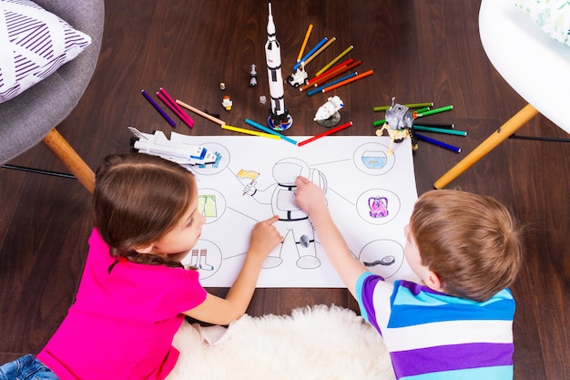 Young children girl and boy painting astronaut costume by pens and dreaming about cosmos with cosmonaut constructor toys
