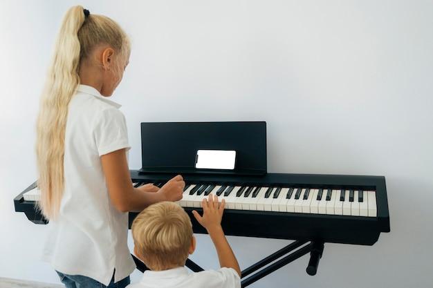 피아노 연주 방법을 배우는 어린 아이들