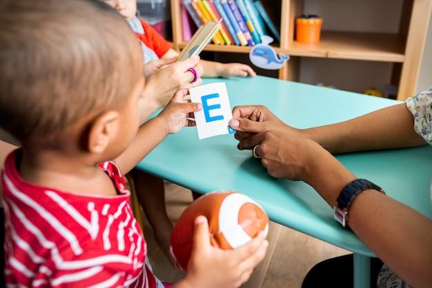 Маленькие дети изучают английский алфавит с родителями