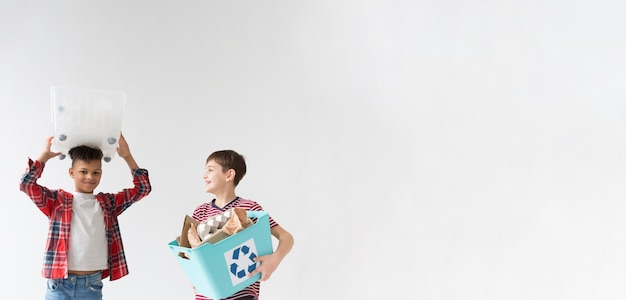 Young children recycling together with copy space