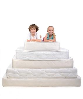 Маленькие дети сидят на большом количестве матрасов.
