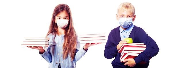 学校でコロナウイルスに対する保護マスクを持っている幼児。