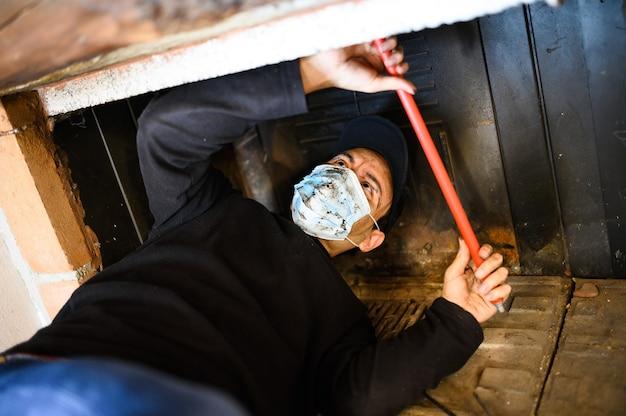 Молодой трубочист на работе и в маске для защиты от пандемии коронавируса covid 19