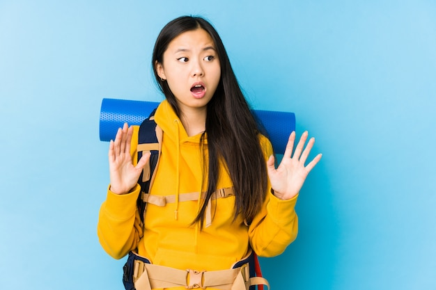 Young chinese backpacker woman isolated being shocked due to an imminent danger