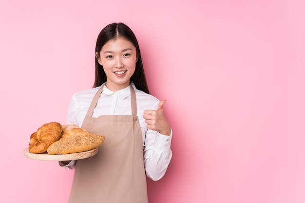 若い中国のパン屋の女性が笑顔と親指を上げる分離