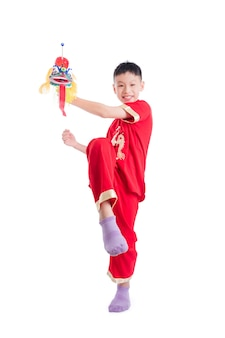 Young chinese boy in red color traditional dress playing chinese lion puppet