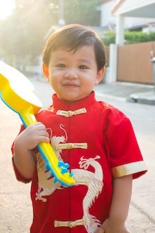중국 새해 의상을 입고 웃고 행복한 어린 중국 소년