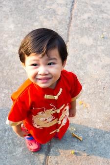 中国の旧正月の衣装ドレスで笑顔で幸せな中国の少年