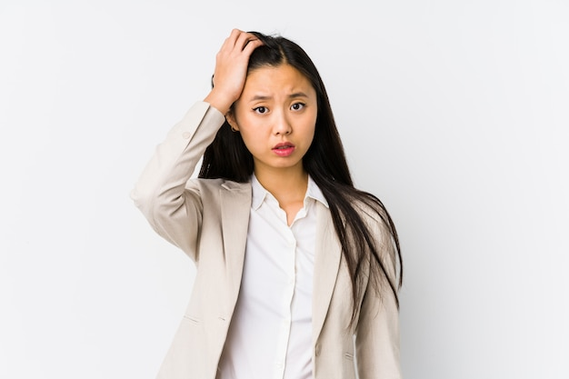 Young chinese business woman isolated being shocked, she has remembered important meeting.