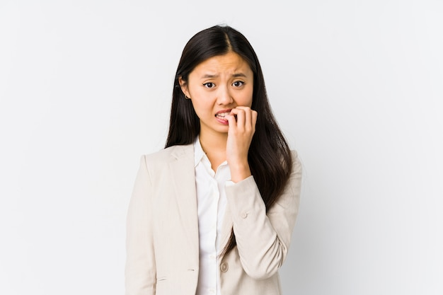 Young chinese business woman isolated biting fingernails, nervous and very anxious.