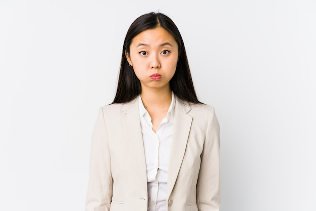 Молодая китайская изолированная бизнес-леди дует щеки, утомленное выражение. концепция выражения лица.