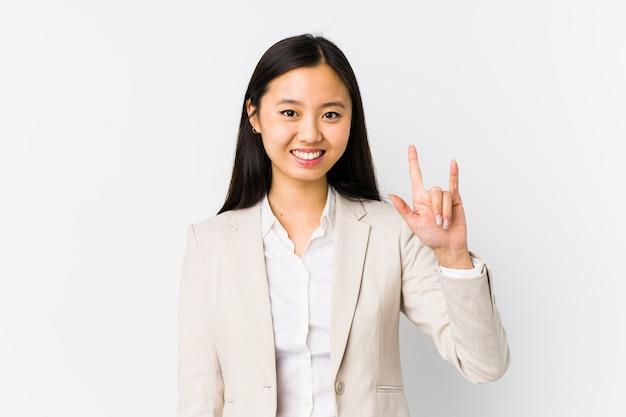 革命の概念として角のジェスチャーを示す孤立した若い中国人ビジネスウーマン。