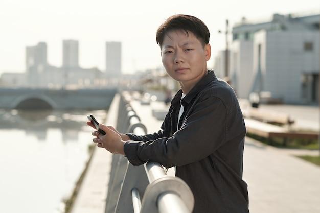 스마트폰으로 당신을 바라보는 젊은 중국 사업가