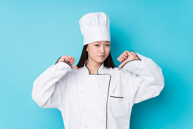 Young chinese chef woman isolated feels proud and self confident, example to follow.