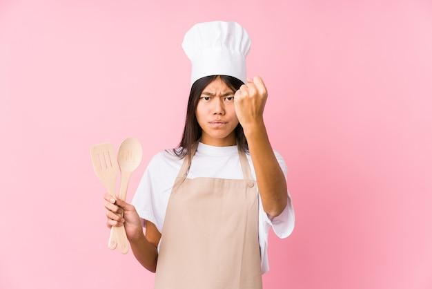 젊은 중국 요리사 여자 절연 보여주는 주먹, 공격적인 표정.