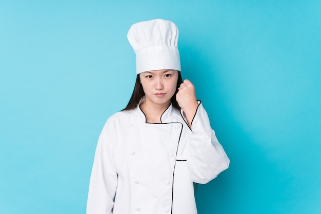 Young chinese chef woman isolated showing fist to with aggressive facial expression.
