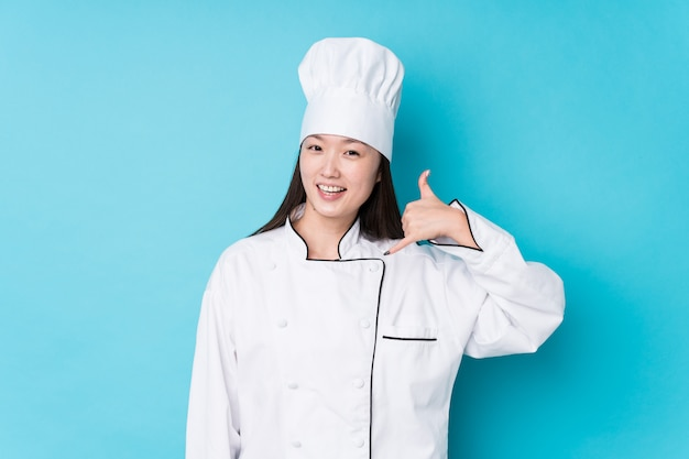 Young chinese chef woman isolated showing a mobile phone call gesture with fingers.