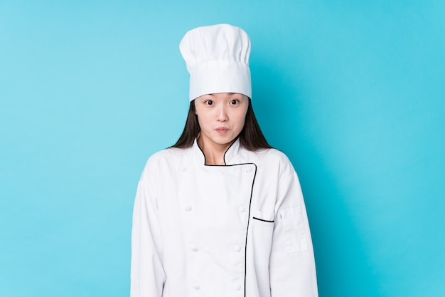 Young chinese chef woman isolated shrugs shoulders and open eyes confused.